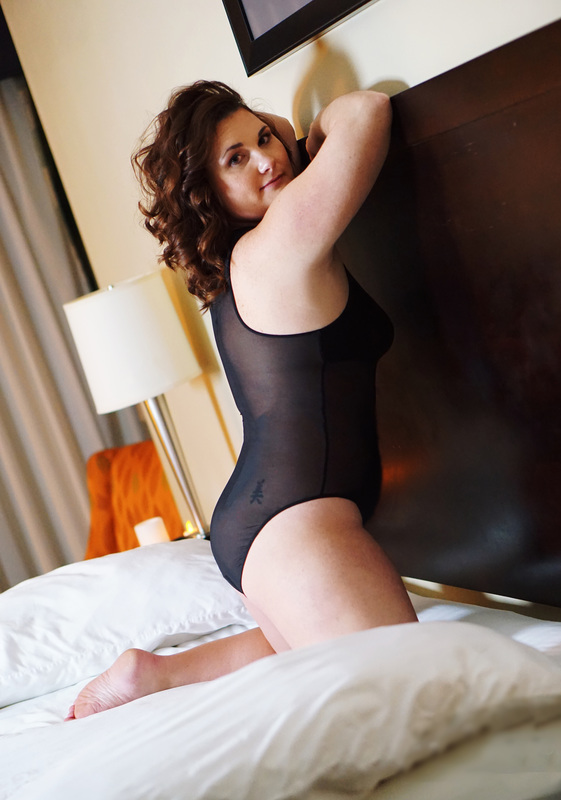 Image of woman in sheer one piece on bed